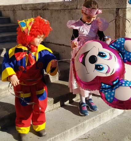 A pint-sized clown, and a petit princess pal around with Mickey.